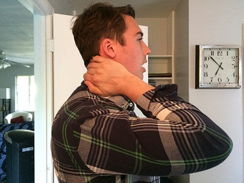 This image shows a singer with his hand on the back of his neck