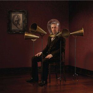man surrounded by old time metal megaphones