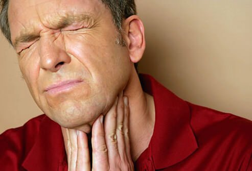 man holding his throat in pain