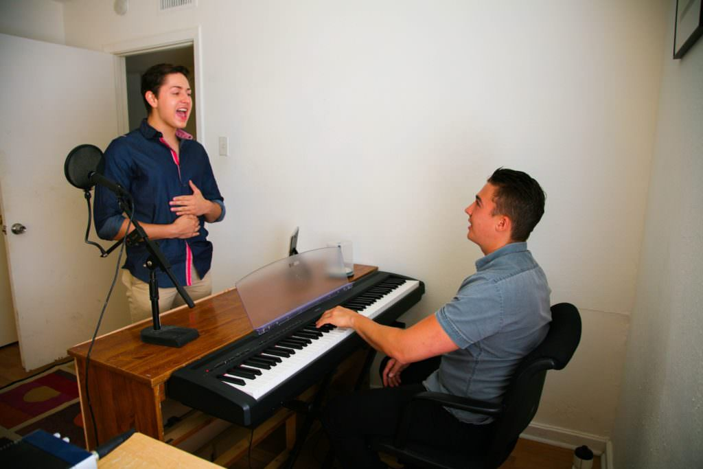 student with voice teacher at piano