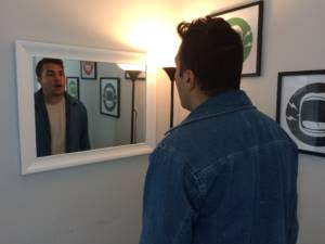 man watching himself sing in the mirror