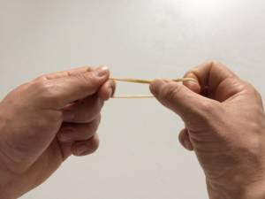 two fingers holding a rubber band loosely between them