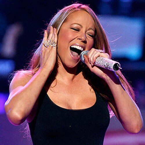 Mariah Carey singing while covering one ear with her hand