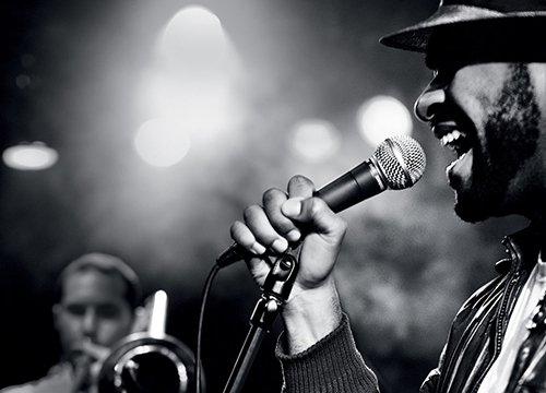 A man singing into a mic in black and white