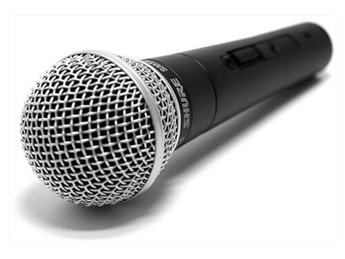 A Schure SM 58 microphone laying on its side with a white background